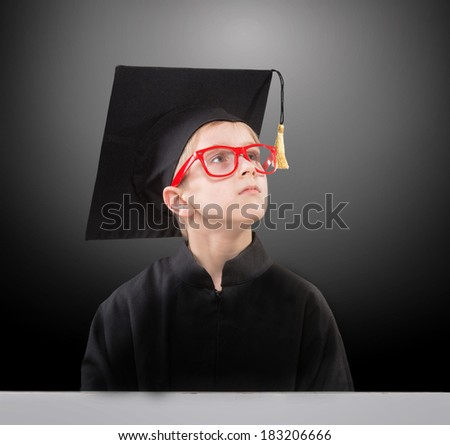 Schoolboy in a mortar board dreaming of his future, dark background - stock photo