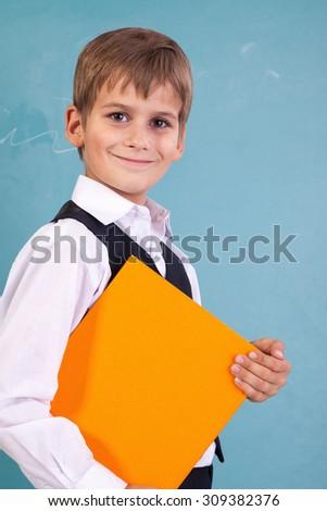 schoolboy is holding an orange book against school blackboard - stock photo