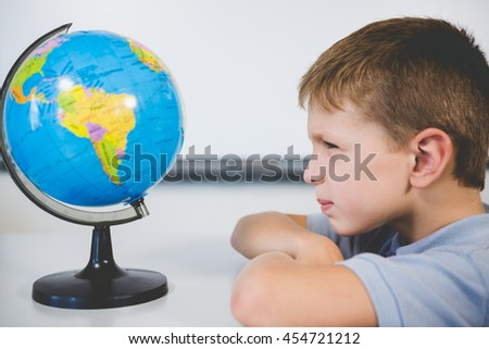Schoolboy looking at globe in classroom at school - stock photo