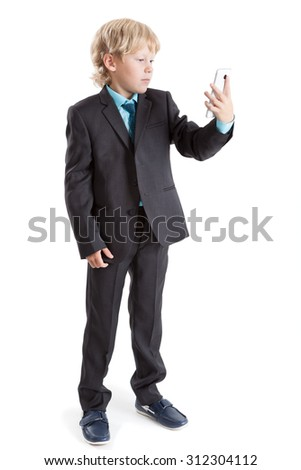 Schoolboy looking at screen of mobile phone while standing full-length on white background, isolated - stock photo