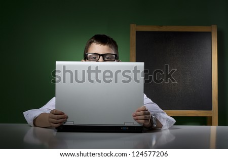 Schoolboy peeps behind computer notebook - stock photo