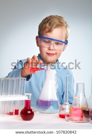 Schoolboy performing a risky experiment with boiling substances - stock photo