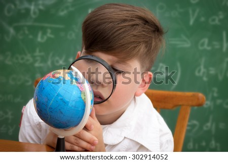 Schoolboy playing with magnifier in geography class. - stock photo