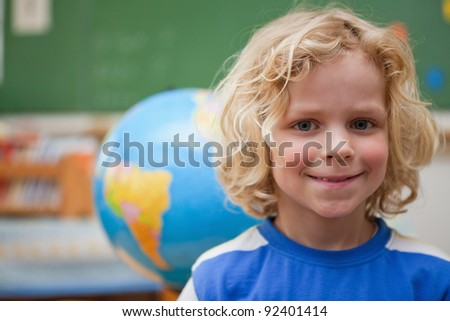 Schoolboy posing in front of a globe in a classroom - stock photo