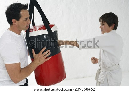 Schoolboy Practicing on Punchbag in Gym Class - stock photo