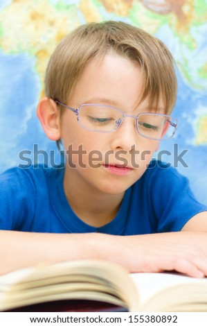 schoolboy reading a book in front of world map - stock photo