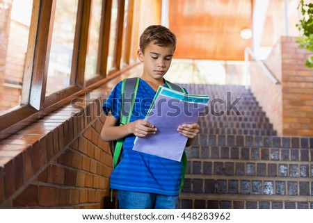 Schoolboy reading a book on staircase at school - stock photo