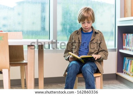 Schoolboy reading book on chair in library - stock photo