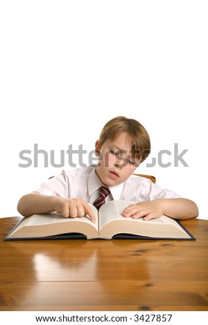 Schoolboy reading from an encyclopedia whilst sat at a desk, isolated on white. - stock photo