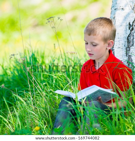 Schoolboy reading the book at  nature - stock photo