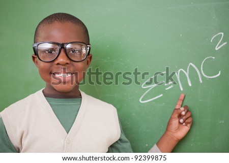 Schoolboy showing the the mass-energy equivalence formula on a blackboard - stock photo