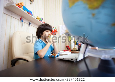 schoolboy sitting at a table with a laptop and eating apple - stock photo