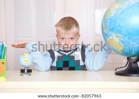 schoolboy, sitting between two globes and surprised, portrait - stock photo