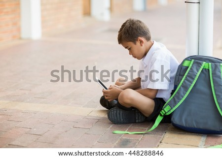 Schoolboy sitting in corridor and using digital tablet at school - stock photo