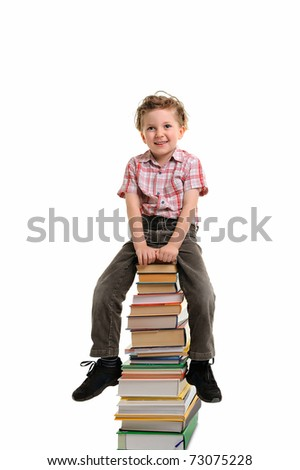 Schoolboy sitting on pile of books. Isolated.