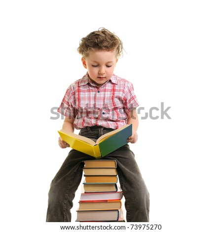 Schoolboy sitting on pile of books. Isolated. - stock photo