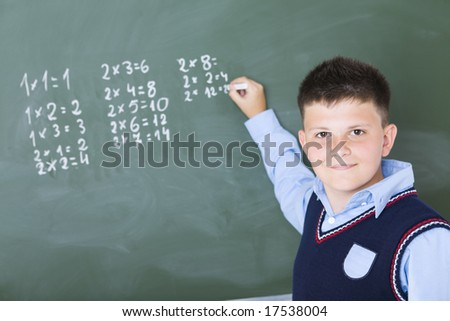 Schoolboy standing and writing something on chalkboard. He's looking at camera. - stock photo