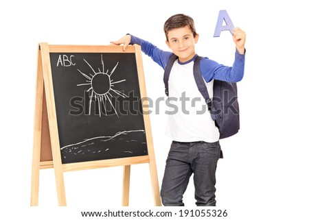 Schoolboy standing by a blackboard and holding the letter a isolated on white background - stock photo