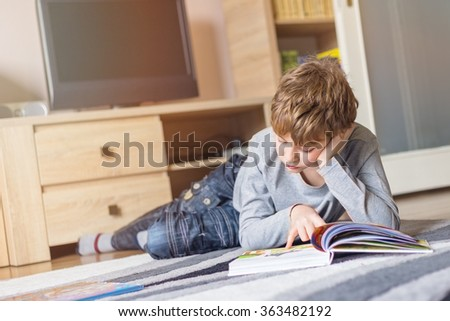 Schoolboy studying in the living room - stock photo