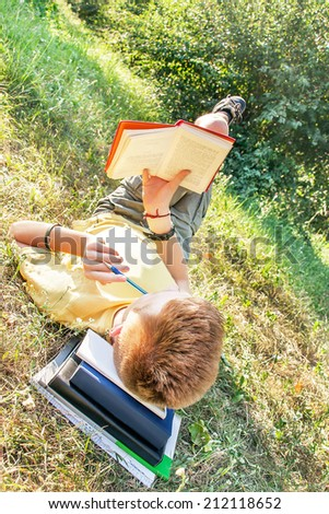 Schoolboy teen (teenager) is lying and reading books for school in the city park. Young smiling red-head boy studying on the grass. Caucasian cute male model (14 year). Sunny day. Education concept.  - stock photo