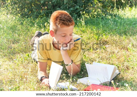 Schoolboy teen (teenager) is lying and reading books in the city park. Young smiling red-head boy studying on the grass. Caucasian cute male model (14 year). Sunny day. Education concept.  - stock photo
