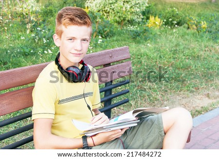 Schoolboy teen (teenager) is sitting with books, head phone on the bench in the city park. Young red-head boy is studying. Caucasian cute male model (14 year). Sunny day. Education concept. Close up. - stock photo
