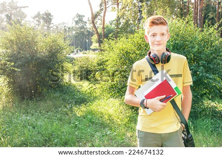 Schoolboy teen (teenager) is standing with books, head phone and school bag in the park. Young child is in the sunny day. Caucasian cute male model (14 year). Education concept. Copy space, outdoors. - stock photo