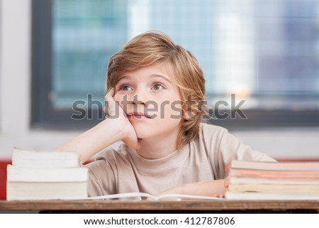 Schoolboy thinking with his books in classroom. - stock photo