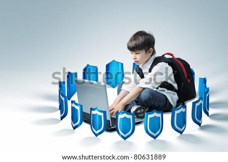 schoolboy use laptop, 3d shields background - stock photo