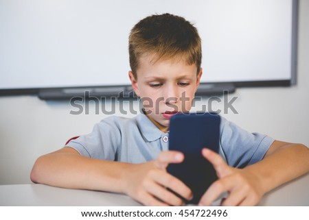 Schoolboy using mobile phone in classroom at school - stock photo