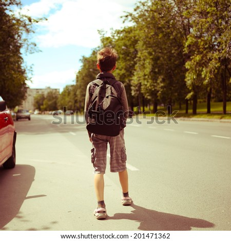 schoolboy walk alone in the street - stock photo