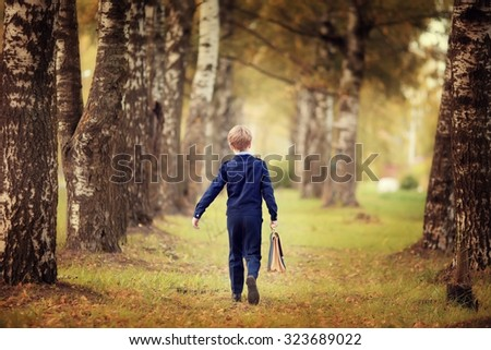 Schoolboy walking alone in the park on a warm autumn day - stock photo