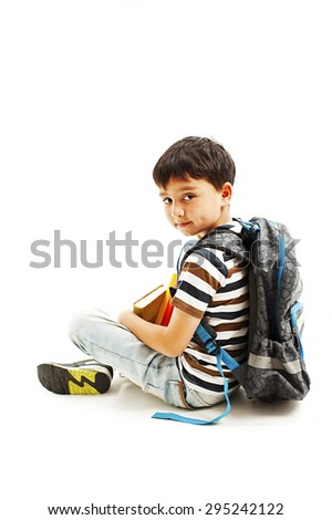 Schoolboy with backpack and book. Isolated on white background - stock photo