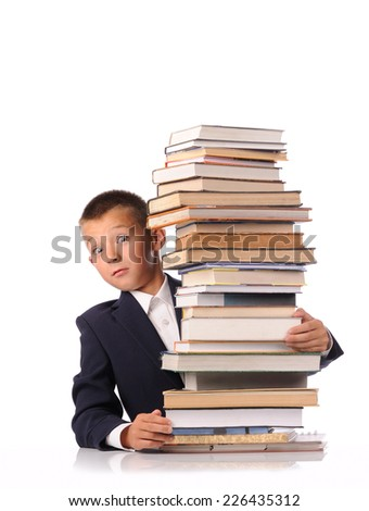 Schoolboy with huge stack of books isolated over white background