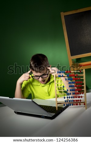 Schoolboy with modern and traditional learning tools - stock photo