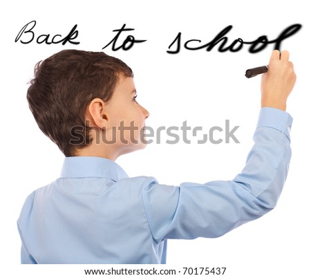 """Schoolboy writing """"back to school"""" on an imaginary board - stock photo"""