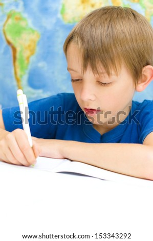 schoolboy writing in his workbook using a pen in front of world map
