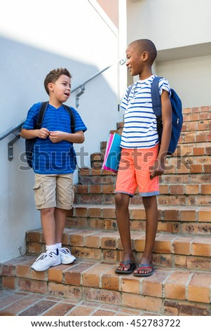 Schoolboys talking while standing on staircase at school - stock photo