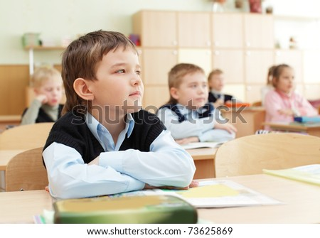 Schoolchild behind desks at school