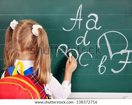Schoolchild writting on blackboard. Rear view. - stock photo