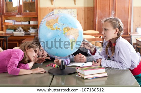 Schoolchildren are exploring globe in classroom during lesson - stock photo