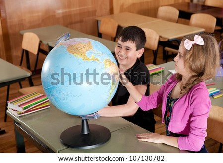 Schoolchildren are exploring globe in classroom during lesson