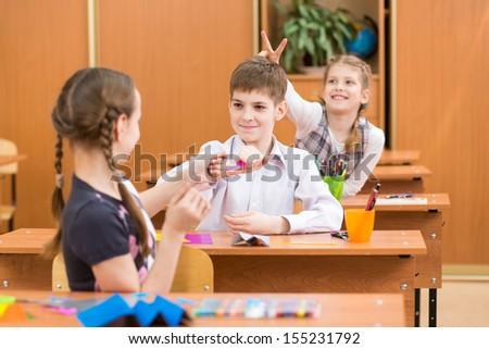 schoolchildren at lesson in classroom - stock photo
