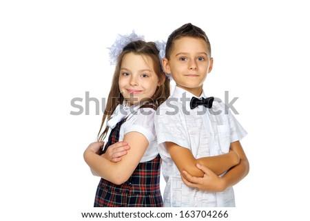 schoolchildren elementary school boy and girl isolated in the studio - stock photo