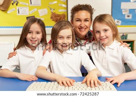 Schoolchildren in IT Class Using Computers with teacher - stock photo