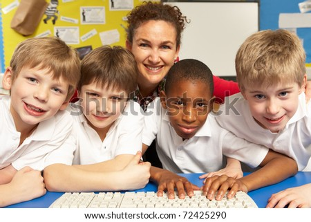 Schoolchildren in IT Class Using Computers with teacher - stock photo