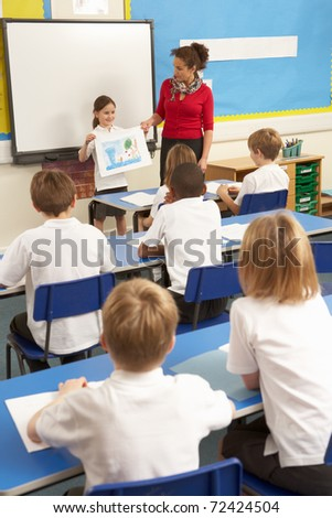 Schoolchildren Studying In Classroom With Teacher - stock photo