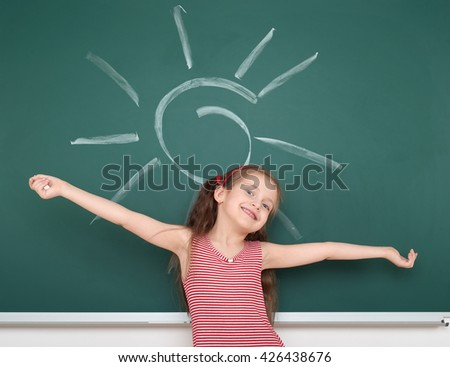 schoolgirl child in red striped dress drawing sun on green chalkboard background, summer school vacation concept - stock photo