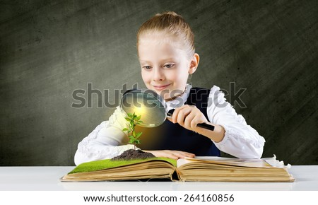Schoolgirl examining opened book with magnifying glass - stock photo