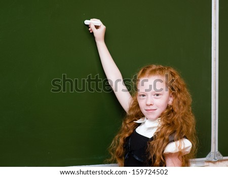 schoolgirl holding a white chalk about to write - stock photo